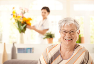 old woman showing her genuine while her caregiver arranging the flowers in flower vase