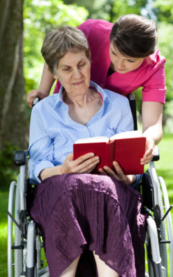 elder woman on wheelchair reading book while the staff assisting her