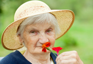 old woman smelling a flower