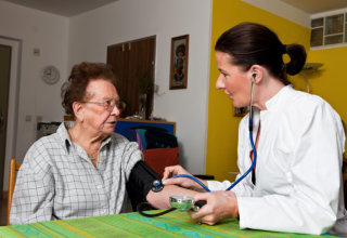 caregiver checking old woman's blood pressure
