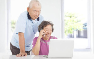 seniors smiling using phone and laptop