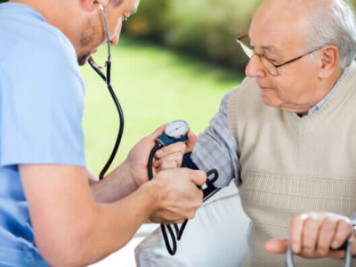 caregiver checking old man's blood pressure