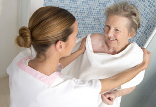 caregiver assisting old woman in bathing