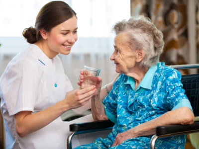 caregiver give a glass of water to the senior woman