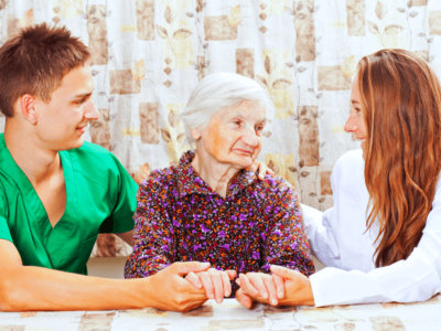 two caregivers are comforting the senior woman