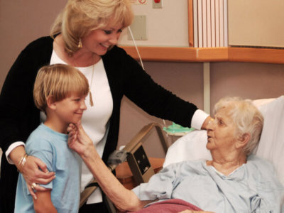 mother and son visit their grandmother on the hospital